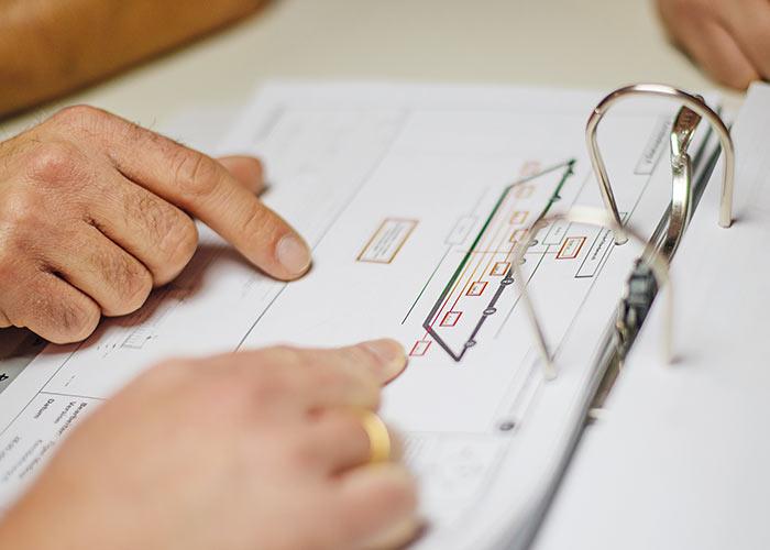 Ein aufgeschlagener Ringordner. Papier ist eingeheftet. Zwei Hände zeigen auf ein Blatt mit einer Zeichnung.
